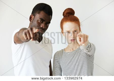 A Couple Of Youngsters Pointing Index Finger In Reproach At Camera. Mix Of Caucasian And African Com