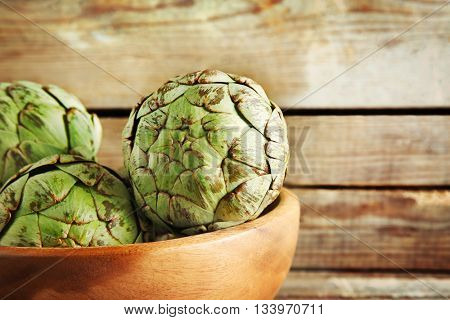 Artichoke in bowl on wooden background
