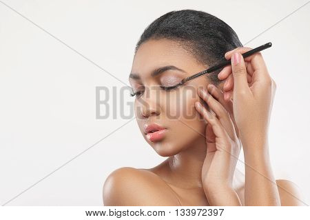 Portrait of attractive young african woman applying eyeshadow on her eyelid. She is standing and holding a brush. Her eyes are closed with relaxation. Isolated and copy space in left side