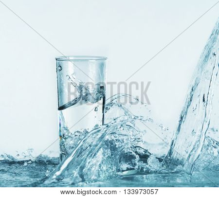 Pouring water into glass on light background