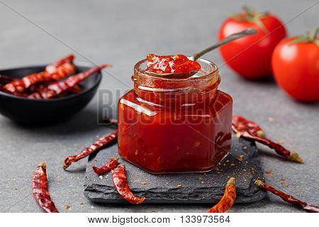 Tomato and chili sauce, jam, confiture in a glass jar on a grey stone background.