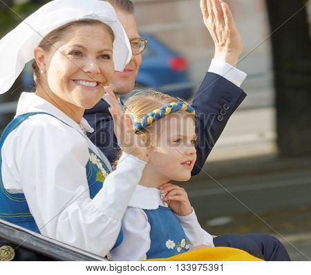 STOCKHOLM SWEDEN - JUN 06 2016: The swedish crown princess Victoria prince Daniel and princess Estelle Bernadotte smiling and waiving to the audience from the royal coach on their way to celebrate the swedish national day.