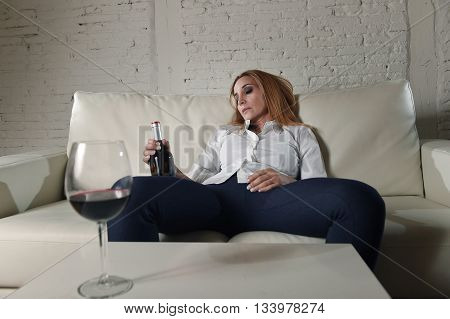 blond sad and wasted alcoholic woman sitting at home sofa couch drinking red wine sleeping drunk looking depressed lonely and suffering hangover in alcoholism and alcohol abuse