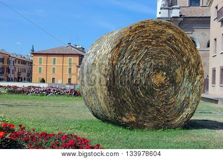 yellow glass art object in a form of cylindrical round artificial haystack on green lawn in Ravenna Italy