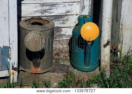 two old watering cans - metal steel grey watering can and plastic green and yellow watering can near the barn outside in countryside