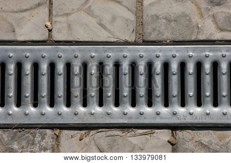 steel metal grey galvanized zinced drainage grate of drainage canal on sidewalk foreground closeup