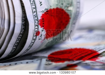 Twisted dollar banknotes with bloodstains, close up