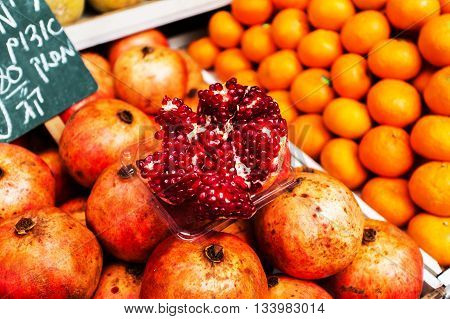 Countertop with a large selection of fruit, cut the pomegranate in the foreground in the Mahane Yehuda Market in Erusalem. Israel