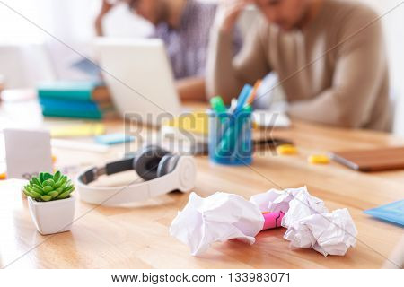 Why is this so hard. Close up of working mess with crumpled paper and headphones on wooden table with two guys in background