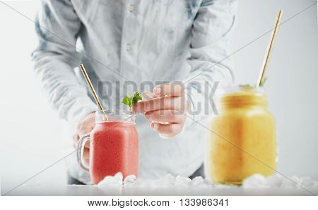 Man Decorates Smoothie In Rustic Jar With Mint Leaves. Two Jars With Healthy Different Cold Fruity S