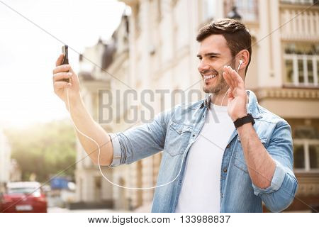 Hey. Cheerful elated smiling man holding cellphone and talking through the Internet while having a walk