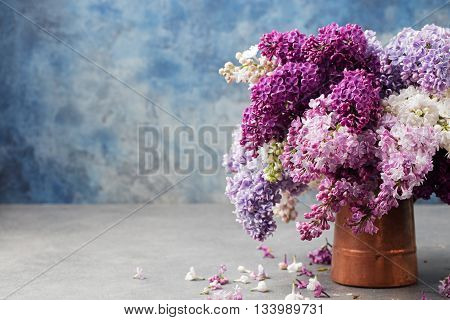 Bunch of lilac flowers in a cooper vintage jug. Blue background Copy space.