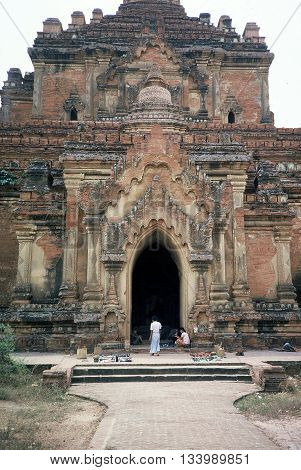 PAGAN BURMA (NOW CALLED MYANMAR) - CIRCA 1987: People relax at the entrance to the ancient Htilominlo Temple in Pagan.
