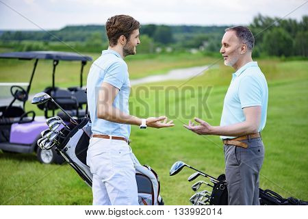 Discussing upcoming game. Two partners discussing upcoming game, standing on green course, holding golf back with golf cart on background
