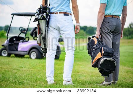 Couple ready to play golf. Close up of golfer partners standing on green golf field and looking into distance, holding golf back with golf cart on background