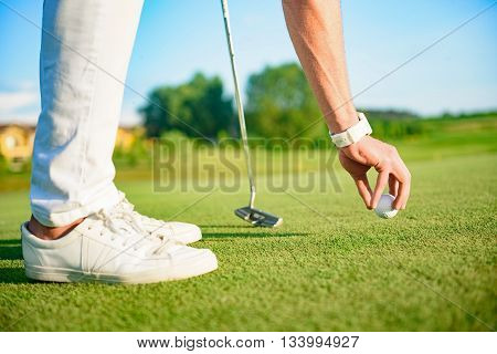 Teeing up. Close up of golfer placing golf ball on golf course, holding driver