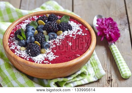 Acai bowl with blackberry, blueberry, coconut and pumpkin seeds