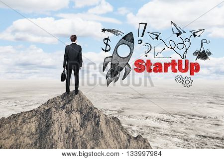 Start up concept with rocket ship sketch and businessman looking at desert from mountain top