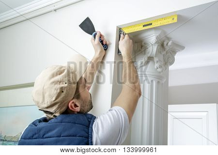 Worker holds putty knife and measures the wall corner using metal angle.  Finishing work. poster