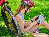 Bikes cycling girl. Girl rides bicycle. Girl in cycling sitting on green grass near bicycle and watch pc tablet. Cycling is good for health. Cyclist looking for road. poster