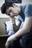Depressed Young Man With Bandaged Wrists After Suicide Attempt poster