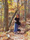 pretty girl hikes through the woods with her dog. poster