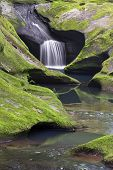 A small waterfall flows through sculpted mossy sandstone above the main plunge of Robinson Falls at Boch Hollow Nature Preserve in Ohio's Hocking Hills. poster