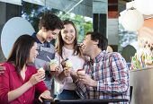 Family Laughing While Having Ice Creams In Parlor poster
