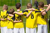 Young sport team with coach on sports field. Football; soccer; handball; volleyball; match for children. Youth sports team standing together. football soccer game. team work and penalty kick poster