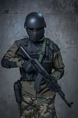 Terrorist soldier in helmet with automatic rifle in hands poster