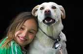 a young girl giving her white dog a hug. poster