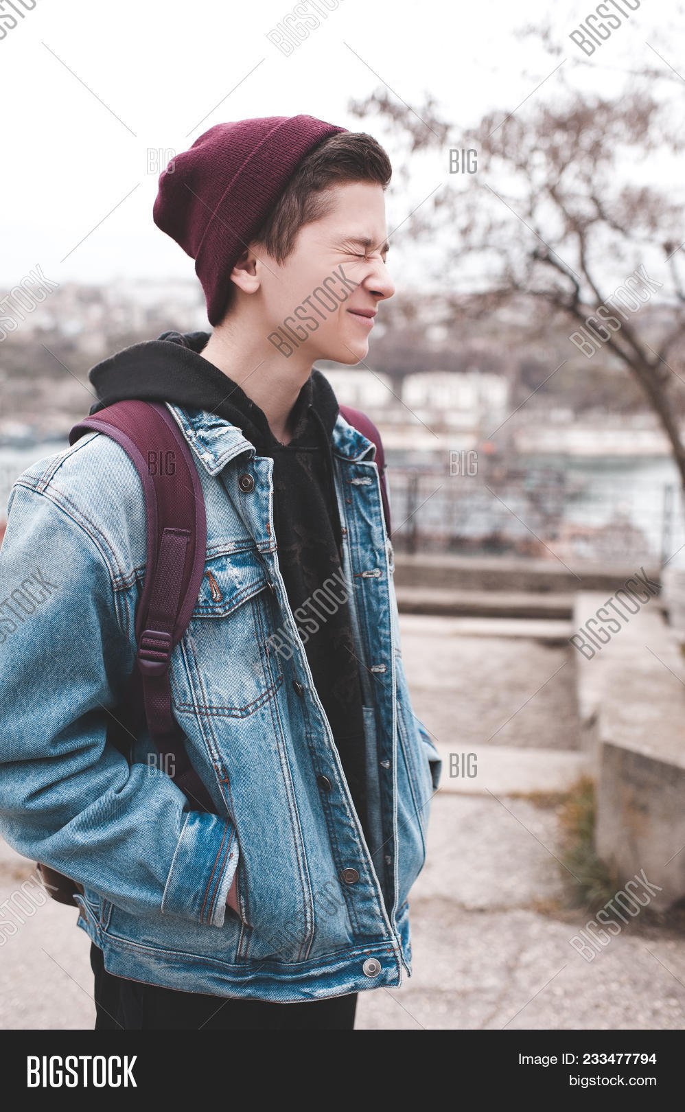 Funny teen boy 14-16 year old laughing outdoors. Wearing denim jacket b795f3ed130