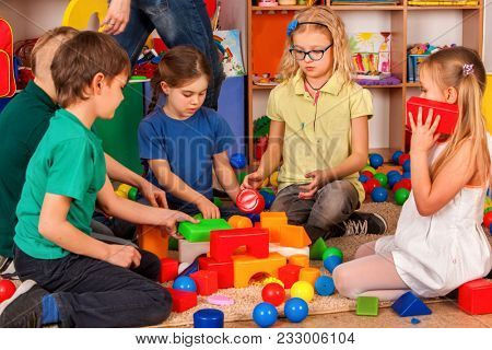 Children building blocks in kindergarten. Group kids playing toy on floor. Top view of interior preschool. Building a tower of cubes. Modern approach to teaching children.