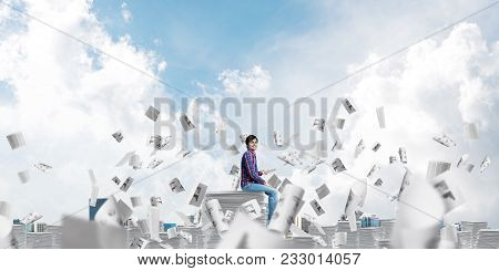 Young Man In Casual Clothing Sitting Among Flying Paper Documents With Cloudly Skyscape On Backgroun