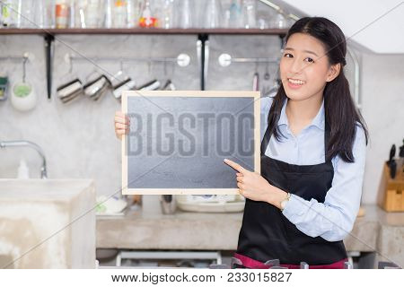Portrait Of Beautiful Young Barista, Asian Woman Is A Employee Standing Holding Chalkboard In Counte