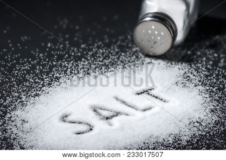 The Word Salt Written Into A Pile Of White Salt And Salt Shaker On Black Table