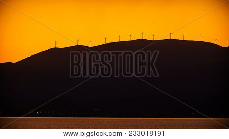 Mountains Power Generators Farm At Sunset. Scenic Sea Landscape With Wind Turbines, Greece. Renewabl