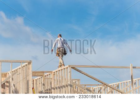 Rear view roofer builder on wooden roof trusses construction. Worker with carpenter tool belt working balancing on roofing. New home site house foundation framing in Irving, Texas, USA poster