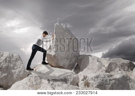 Business Concept, Young Businessman Pushing Large Stone Uphill With Copy Space.