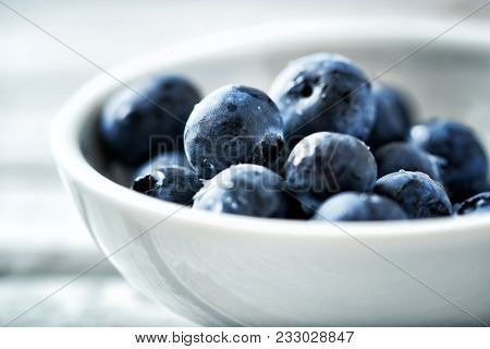 Freshly picked bilberries in white, ceramic bowl on white, wooden background. Concept for healthy eating and nutrition. Close up. Horizontal.