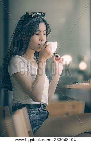 Portrait Of Young Woman Closed Her Eyes And Drinking Coffee In Cafe With Happiness