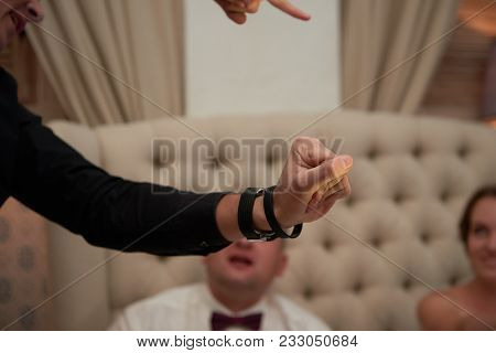 Close Up Magician Points At Watch During Tricks At Wedding Ceremony