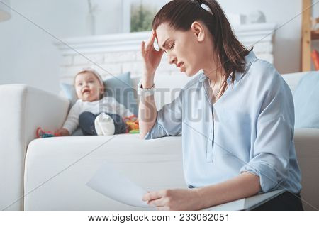 So Stressed Out. Sad Cheerless Tired Woman Sitting On A Sofa And Holding Her Head While Having A Hea