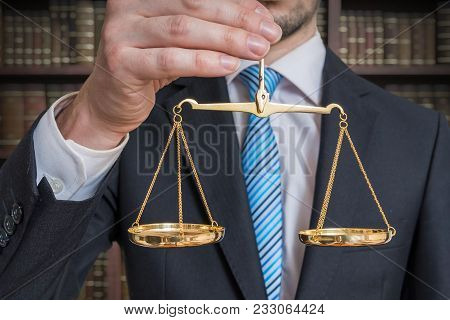 Law And Justice Concept. Lawyer Is Holding Justice Scales In Hand.