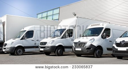 Delivery White Vans In Service Van Trucks And Cars In Front Of The Entrance Of A Warehouse Distribut