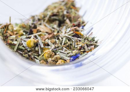 Dried Herbal Chamomile Tea Leaves In Transparent Glass Jar On Light Background