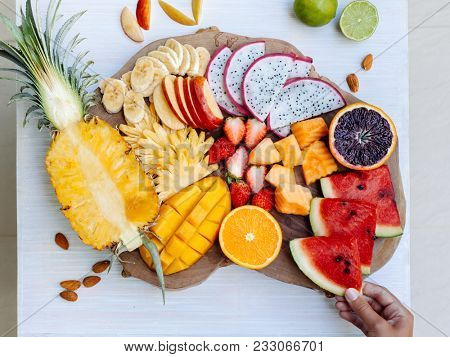 Many sliced colorful tropical fruit plate on serving tray, top view from above. Summer healthy diet, vegan breakfast. Woman hand taking watermelon slice - POV.