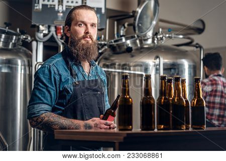 Tattooed Bearded Caucasian And Indian Men Presenting Craft Beer In The Microbrewery.