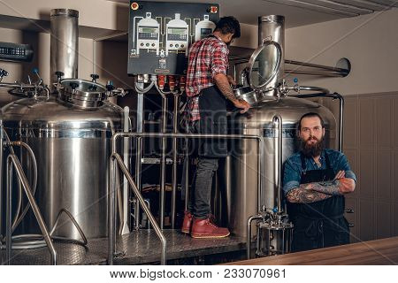 Portrait Of Tattooed, Bearded Caucasian And Indian Men In The Craft Beer Microbrewery.