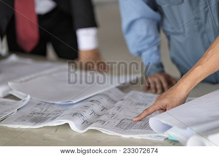 Architect With Businessman And Engineer Are Planning On Blueprint. Architect Is Pointing On The Blue